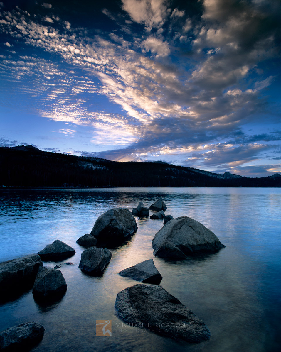 A blue sunset falls over the pine forest and granite domes of Courtright Reservoir, Sierra National Forest.Logos and watermarks...