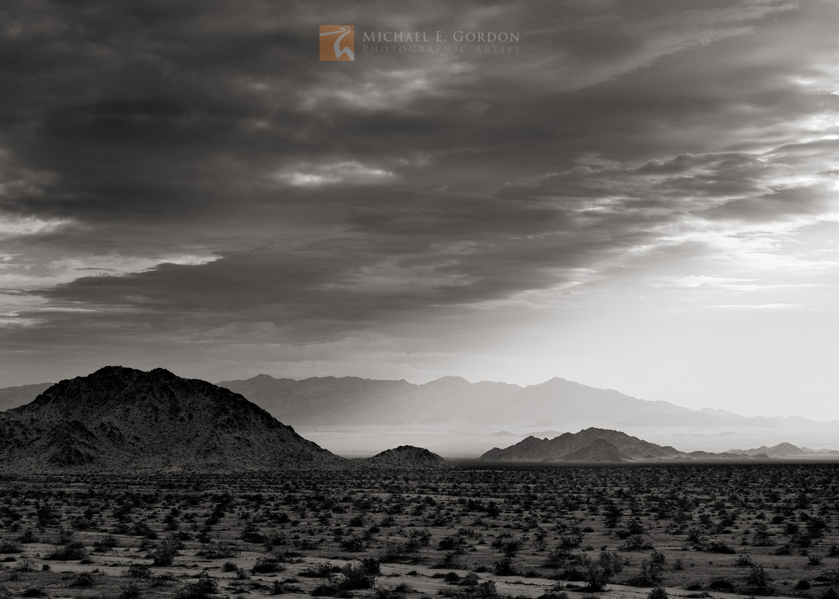 black and white, fine art photograph, fine art print, photo, picture, Sheephole Valley, clouds, lightshow, dappled light, Mojave Desert, photo